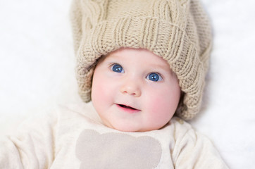 Cute newborn baby wearing a big knitted hat and a wam sweater
