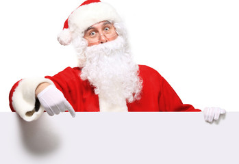 Santa Claus pointing in white blank sign with smile