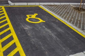 Handicap symbol painted on asphalt at parking space