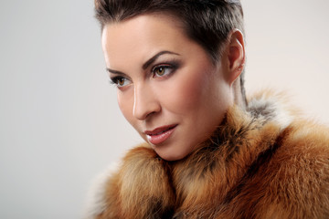 Glamour and gorgeous brunette and her fur coat on