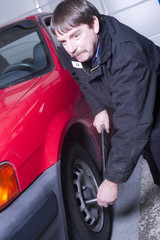 Automotive Technician Auto Mechanic Loosens Lug Nut Front Tire