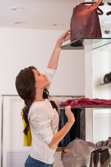 Young pretty woman reaching for a bag on high shelf at store whi