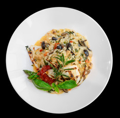 Risotto with tomatoes and herbs in plate, isolated on black