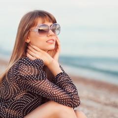 fashion girl sitting on the beach wearing sunglasses