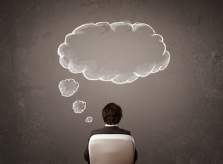 Businessman sitting with cloud thought above his head