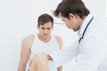 Displeased young man getting his leg examined