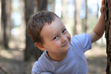 Funny boy 3-4 old at tree in the forest