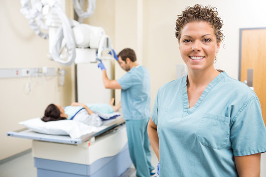 Nurse Smiling While Colleague Preparing Patient For Xray