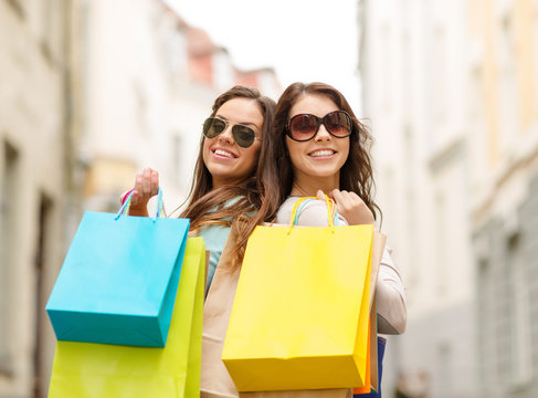 two girls in sunglasses with shopping bags in ctiy