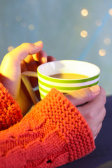 Hands holding mug of hot drink, close-up, on bright background