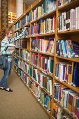 Redhead student taking book from bookshelf in the library