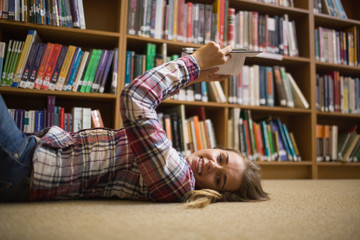 Pretty happy student lying on library floor reading book