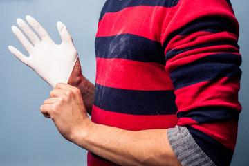 Man putting on latex glove
