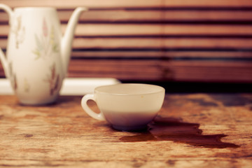 Coffee cup and pot by window on wood table