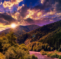 Mountain river near forest at sunset