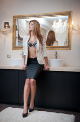 Sensual elegant woman in office outfit staying near a mirror