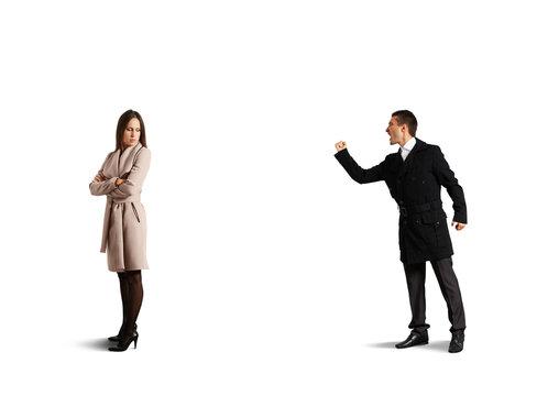 emotional man screaming at sad woman