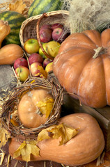 Pumpkins and apples in basket with watermelons on straw close