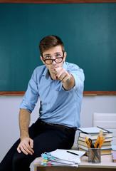 Young teacher sitting on desk in school classroom