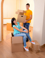 Young couple fooling around in new house on room background
