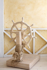Beautiful wooden ship wheel with wire rope in light room