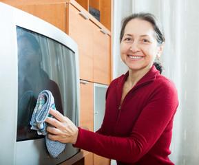 mature woman dusting TV