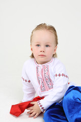 Little cute boy in Russian national costume sits on floor