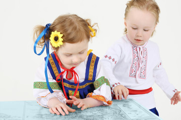 Little boy and girl in Russian national costume look at big map