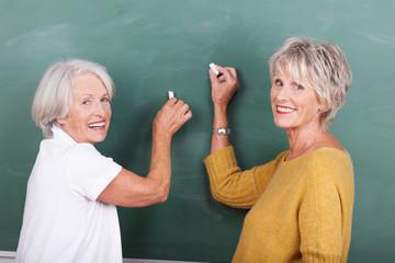 zwei seniorinnen schreiben an die tafel