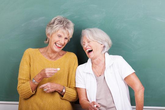 lachende seniorinnen vor einer schultafel