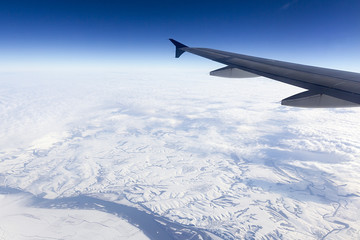 Flying above mountains: snow below