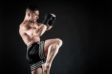 Sportsman kick boxer fighting against black background.