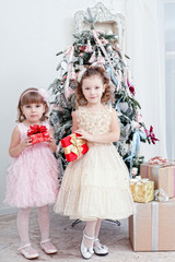 Two little girls with gifts near a Christmas fir-tree