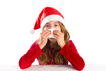 Christmas Santa kid girl blowing her nose in a winter cold