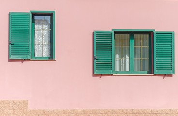 Two window with open green shutters