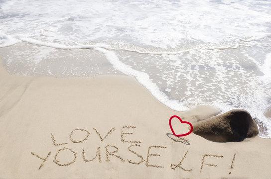 "Sign ""Love yourself"" on the sandy beach"