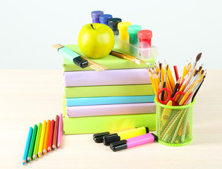 School supplies on table on blackboard background