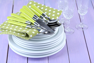 Clean dishes on wooden table on color background