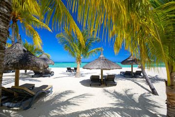 Wall Mural - Lounge chairs with umbrellas on white sand beach, Mauritius