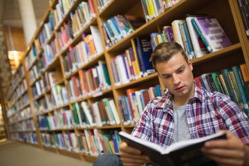 Focused young student sitting on library floor reading book