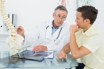 Doctor explaining spine to patient in office