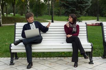 Курящая девушка и мужчина сидят рядом в парке на скамейке