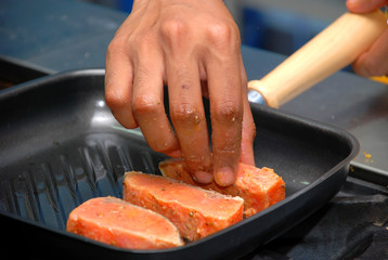 Chef is putting salmon fillet on hot pan, close-up. Shallow DOF
