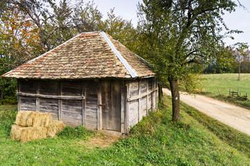 Old wooden barn by a gravel mountain road, Bobija mountain