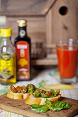 Toasts with tomato and basil on a wooden board