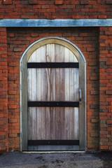 old wood barn door with brick wall
