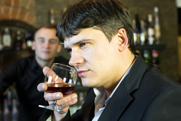 young man drinking brandy at the bar
