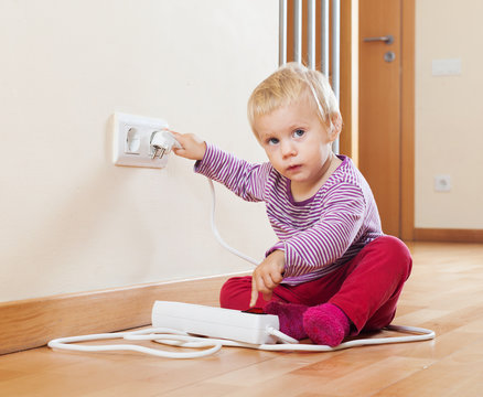 Baby playing with electrical extension and outlet