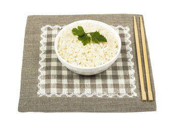 A plate of rice and chopsticks on linen tablecloth, isolated