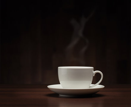 Close up of coffee cup on the table over dark background